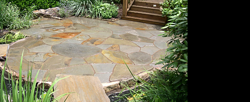 Each flagstone set in this circular patio was re-cut to create soft curving joints to complement the curves of the adjoining water feature and curved stone walls
