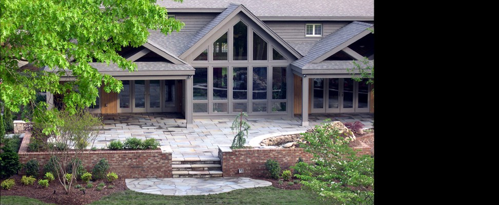 This grand patio design was constructed of Pennsylvania full-color pattern flagstone with serpentine cut natural capstone over synthetic stone seating walls and steps, and provides a spacious outdoor living and entertaining area for the home.  A irregular-flagstone organic design patio transitions to the lush lawn and landscape.