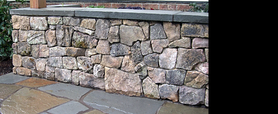 This is an example of an extremely tight natural stone veneer wall installed on a concrete slab and block foundation and features a two inch bluestone flamed capstone