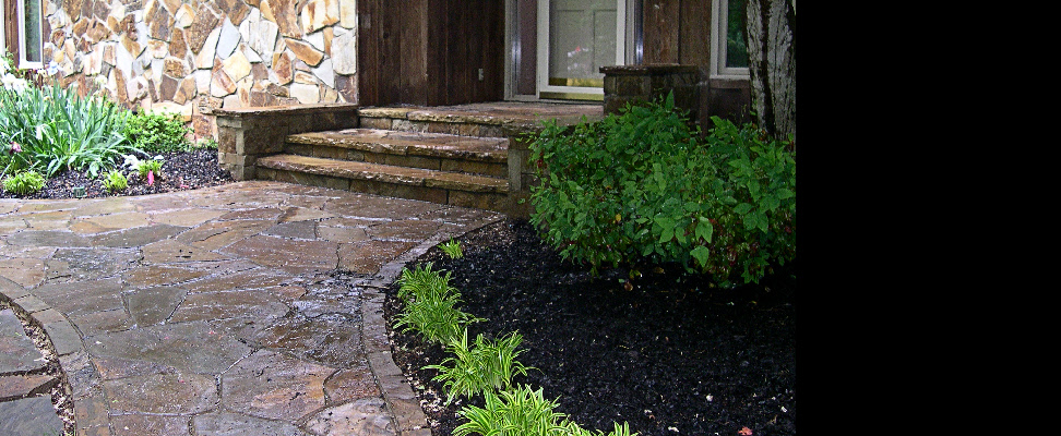 A beautiful natural stone walk, steps, side walls, and landing replace a wooden porch
