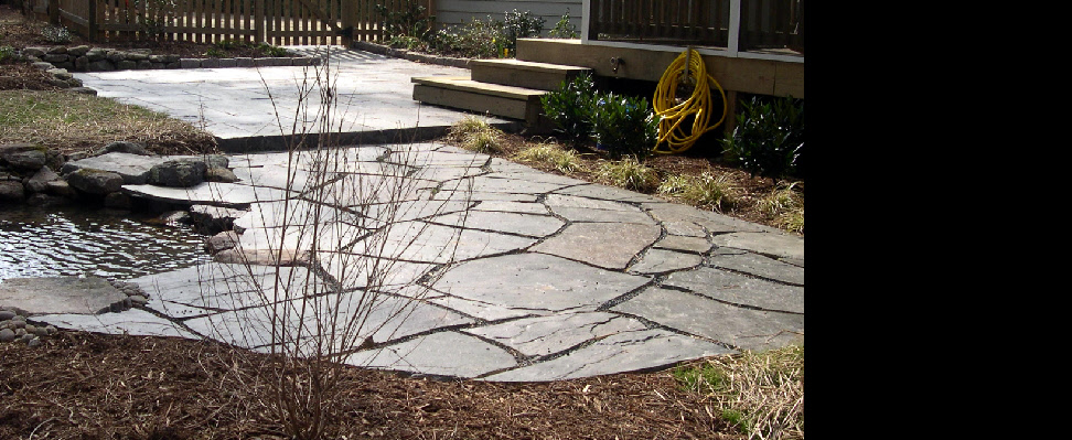 This two tiered patio features both pattern flagstone (on slab) with mortar joints and an adjoining irregular flagstone (on compacted base) with gravel joints