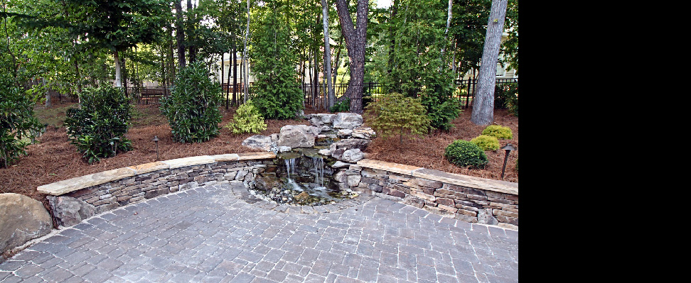 This hardscape features a natural recirculating stream with waterfall breeching a natural stone seating wall, bouldering, stone steps and pavers patio