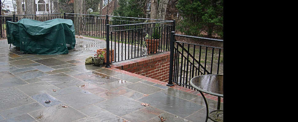 A beautiful upgrade to a wooden deck overhaul using Pennsylvanin pattern flagstone and a brick foundation