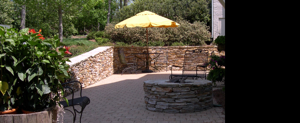 A natural stone retaining wall with natural gas fire pit--a great place to be day and night