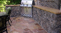Natural stone built-in cook center and flagstone patio