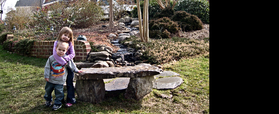 The grandchildren enjoy playing in this stream featuring a small patio and natural stone bench