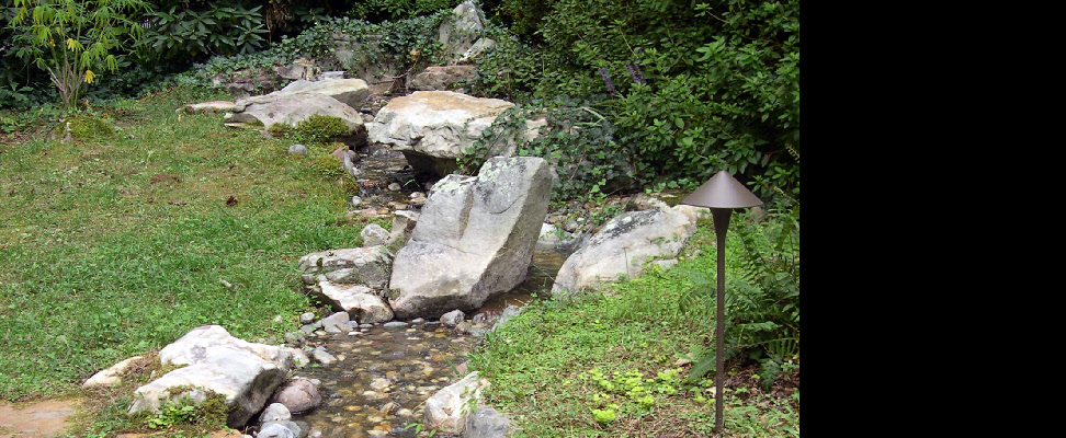 This natural looking brook runs beside a flagstone patio and stone bench