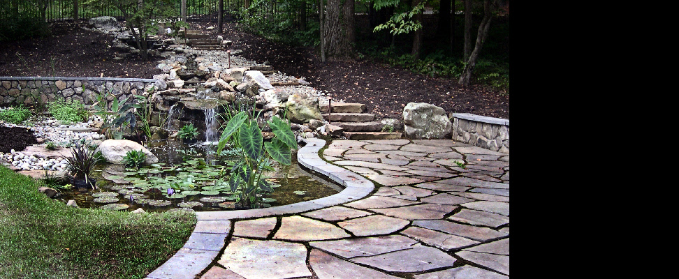 This comprehensive stone/water-scape features hillside stream, bog garden, multiple falls, bouldering, seating wall, and a patio with Pennsylvania bluestone coping